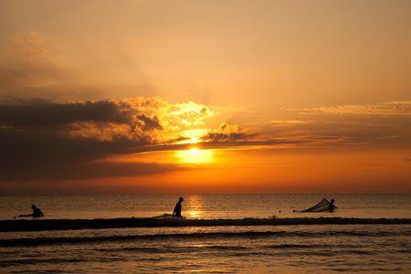 Silhouettes Of Fishermen  On The Sunrise Background Stock Photo - 6487095
