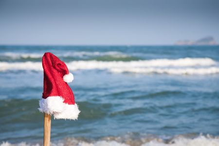 Christmas hat against blue sea. Christmas collection. photo