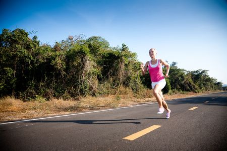 girl action: Blond young woman running cross country. Subject is blurred due to motion. Stock Photo