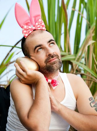 Man Wearing Rabbit Hat mit Big Golden Egg Standard-Bild