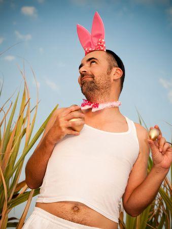 ostern lustig: Man Wearing Bunny Hut mit goldenen Eier In den H�nden Lizenzfreie Bilder