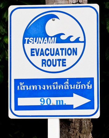 A tsunami warning sign located near a beach in Phuket, Thailand photo