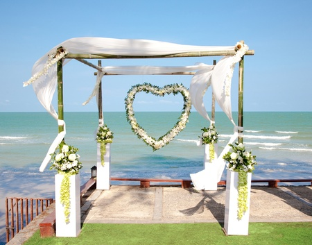 honeymooners: Wedding arch with flowers decoration on the beach