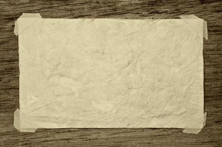 Old grunge paper on the dark wood background photo