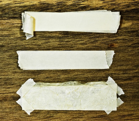 Torn paper and tape on wood wall Stock Photo - 9319679