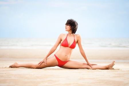 Beautiful woman doing yoga and stretches exercise on the beach photo