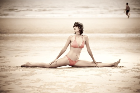 Beautiful woman doing stretches exercise on the beach. Retro Series