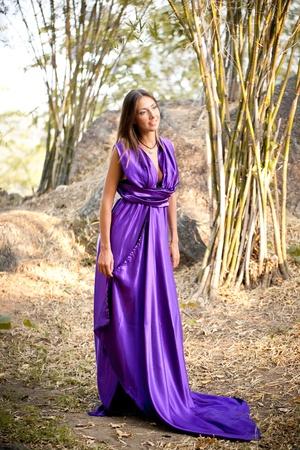 Beautiful woman wearing a long purple dress. photo