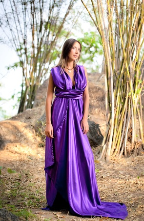 Beautiful woman wearing a long purple dress. Bamboo grove. Thailand photo