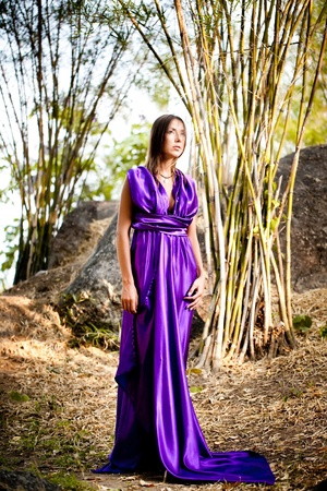 Beautiful young woman in purple long dress. Bamboo grove. Thailand photo