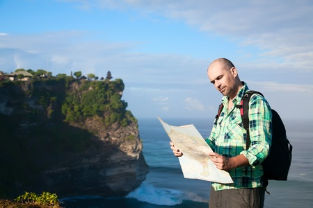 Man tourist with map at the beachfront photo