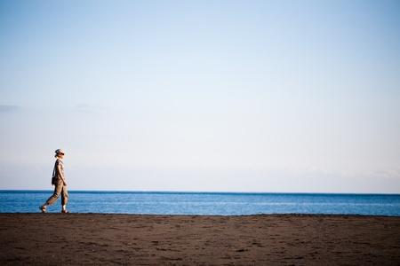 Woman walking along the black sand beach
