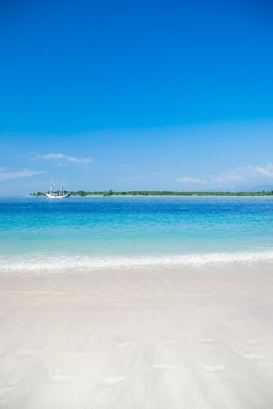 the clear sky: Tropic playa de la isla con barco en el fondo. Gili, Indonesia Foto de archivo