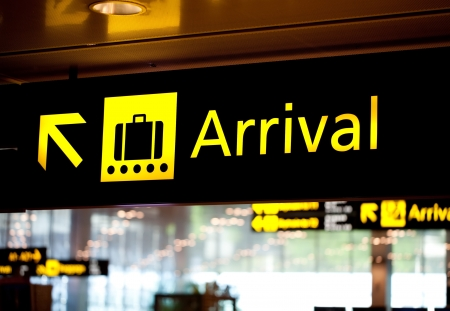 passenger: Brightly light arrival airport information sign Stock Photo