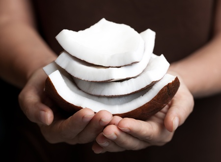 Coconut held by a woman hands. SPA collection. Stock Photo