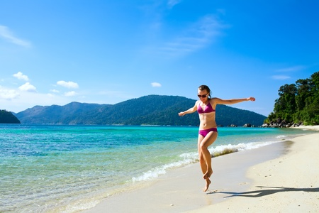 Happy Woman running along tropical island beach Stock Photo - 11991638