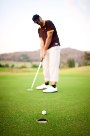 Ball near the hole and golfer on background photo