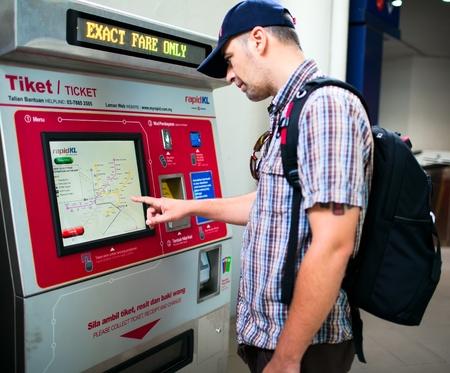 KUALA LUMPUR - 29 de noviembre: la compra de pasajeros billete de metro en la máquina automática. 29 de noviembre 2011 en Kuala Lumpur, Malasia.