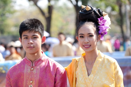 CHIANG MAI, THAILAND - FEBRUARY 4: Traditionally dressed smiling man and woman on Chiang Mai 36th Flower Festival on February 4, 2012 in Chiang Mai, Thailand