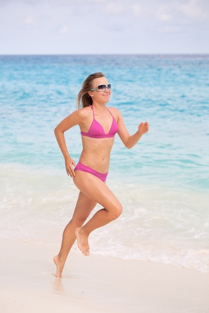 Woman Jogging on White Sandy Beach photo