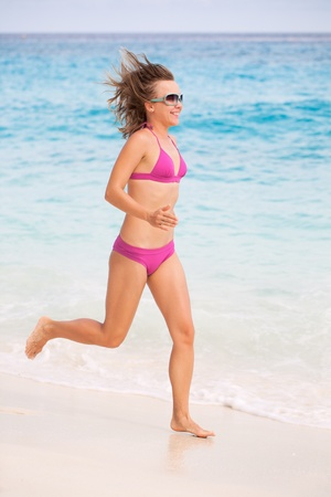 Young Woman Running On The Beautiful Beach photo