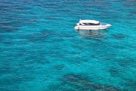 Speedboat anchored in crystal clear watar photo