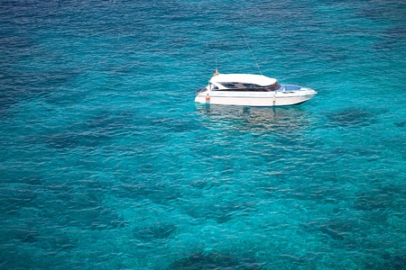 Speedboat anchored in coral reef sea photo