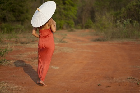 Woman in red dress walking with umbrella photo