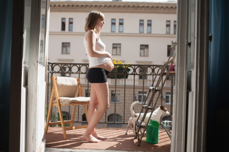 Beautiful pregnant woman on the balcony photo