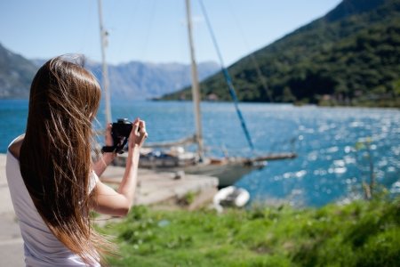 people travelling: Woman takin a photo of yacht Stock Photo