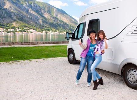 motorhome: Happy young womans outside motorhome Stock Photo