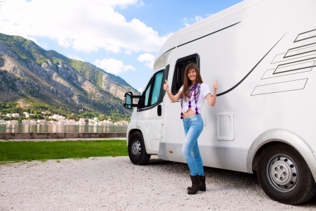 recreational vehicle: Portrait of a happy young woman standing in front of motor home