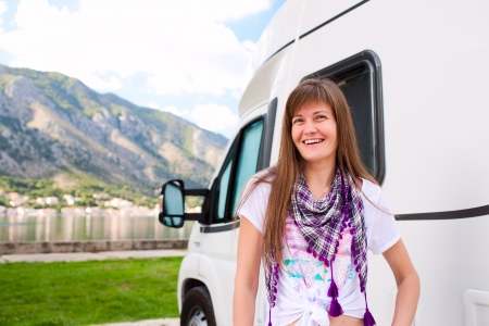 Happy young woman standing in front of camper