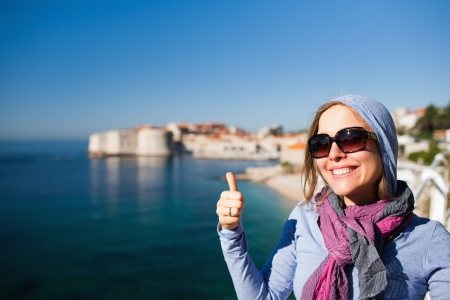 Tourist woman against Dubrovnik old town giving the thumbs up photo