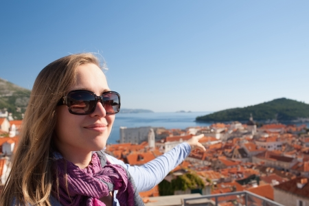 sightseeng: Tourist woman looking at Dubrovnik from the city walls
