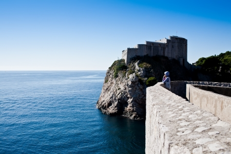 sightseeng: Woman looking over the sea from the city walls Stock Photo