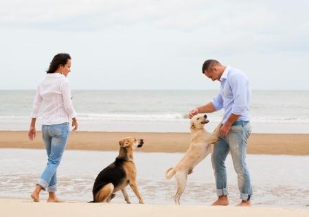 mujer perro: Retrato de una pareja feliz con los perros en la playa Foto de archivo