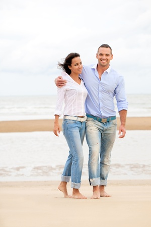 Happy young couple enjoying a solitary beach photo