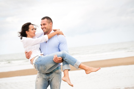couple holding hands: Happy young couple enjoying a solitary beach