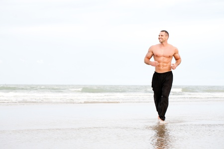 excercise: Young handsome muscular man running on the beach Stock Photo