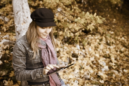sepia toning: Woman with Digital Tablet in autumn forest, Sepia toning Stock Photo