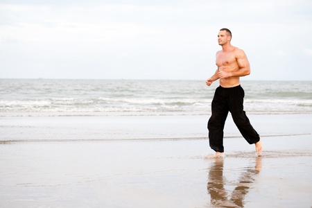excercise: Physically fit man running on the beach Stock Photo