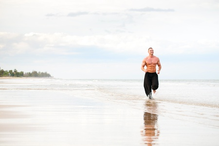 physically: Physically fit man running on the beach Stock Photo