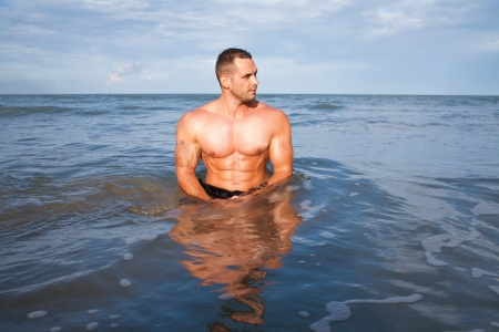 Strong young man portrait at the beach photo