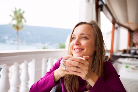 A smiling woman in a restaurant is drinking coffee photo