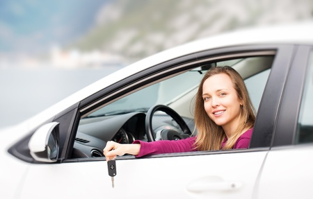 Young woman with keys of new , hire or rental car photo