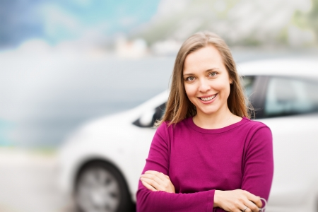 Young woman standing near new car photo