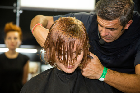 snipping: MOSCOW - OCTOBER 24: Hairstylist performs hair cut at the international exhibition of professional cosmetics and beauty salon equipment INTERCHARM on October 24, 2014 in Moscow