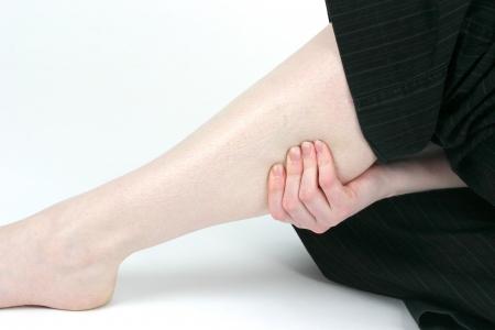dolor muscular: Mujer que sostiene un m�sculo dolorido de la pierna