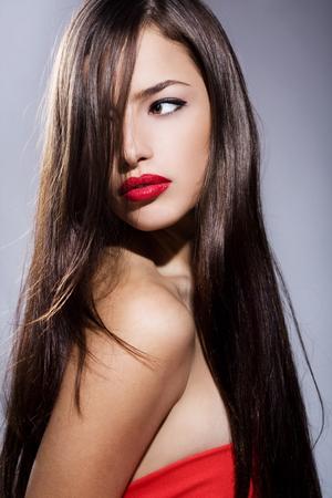 capelli lunghi: bei capelli lunghi giovane donna con labbra rosse e abito Archivio Fotografico